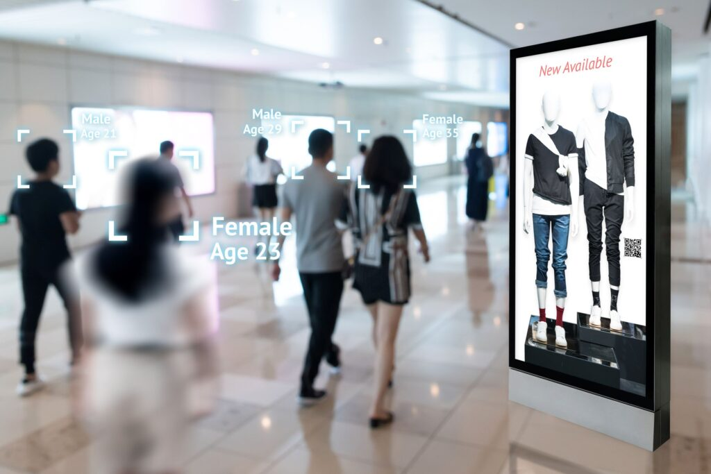 Tall, vertical digital sign displaying 2 people in trendy fashion. The sign is located in a busy corporate hallway with people walking by.
