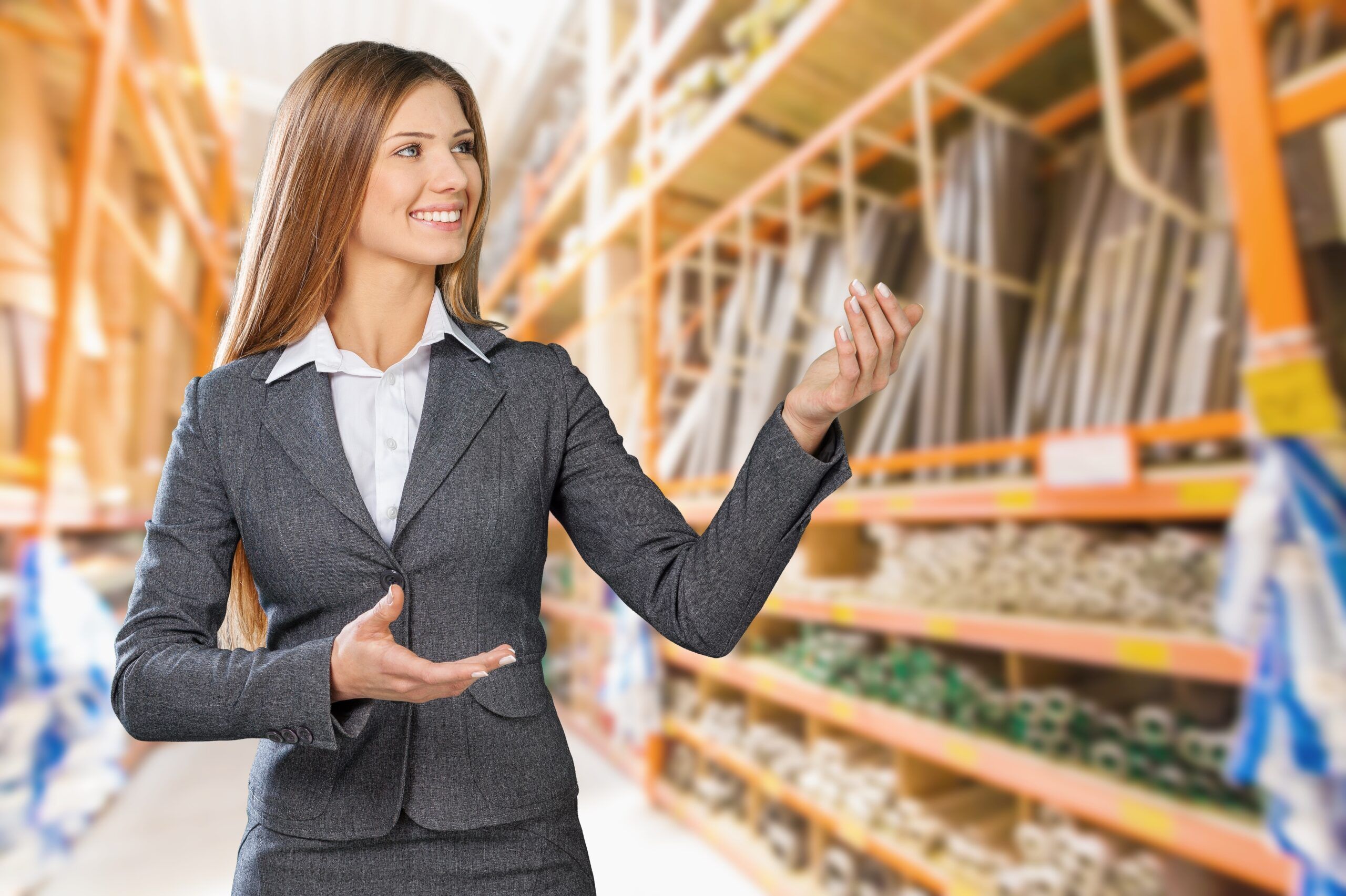 Woman in grey business suit in big box hardware store pointing to products on shelves