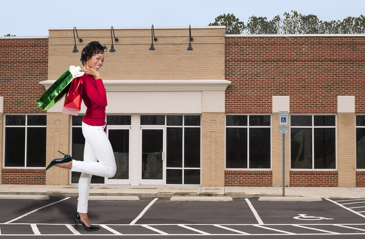 Beautiful woman in red shirt and white pants walking with shopping bags in front of storefront