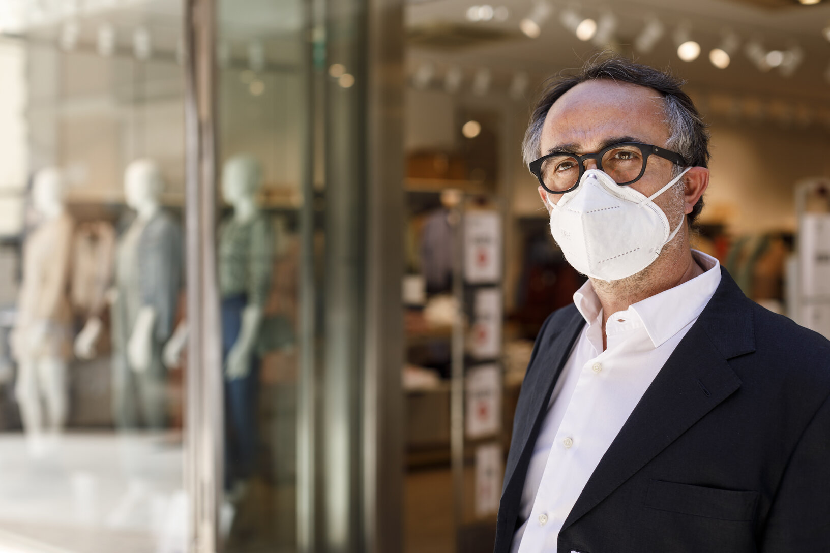 Man in suit and facemask standing outside a storefront