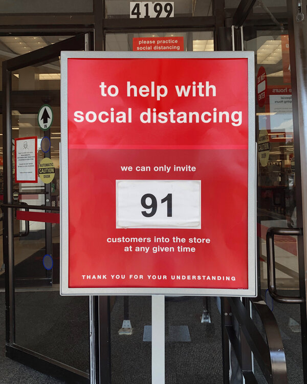 A red sign with social distance text showing the amouont of customers that can be in the store at one time for a pandemic shopping idea.